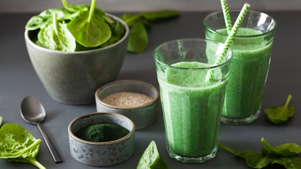 A collection of green and healthy foods laid out on a table including spirulina